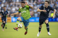 Seattle Sounders midfielder Cristian Roldan attacks the ball past Sporting Kansas City defender Andreu Fontas during the first half of an MLS soccer match, Sunday, Sept. 26, 2021, in Kansas City, Kan. (AP Photo/Nick Tre. Smith)
