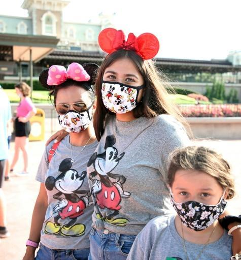In hard-hit Florida the Walt Disney World theme park partially reopened after four months of shutdown, with some visitors combining Mickey ears with their mandatory face masks