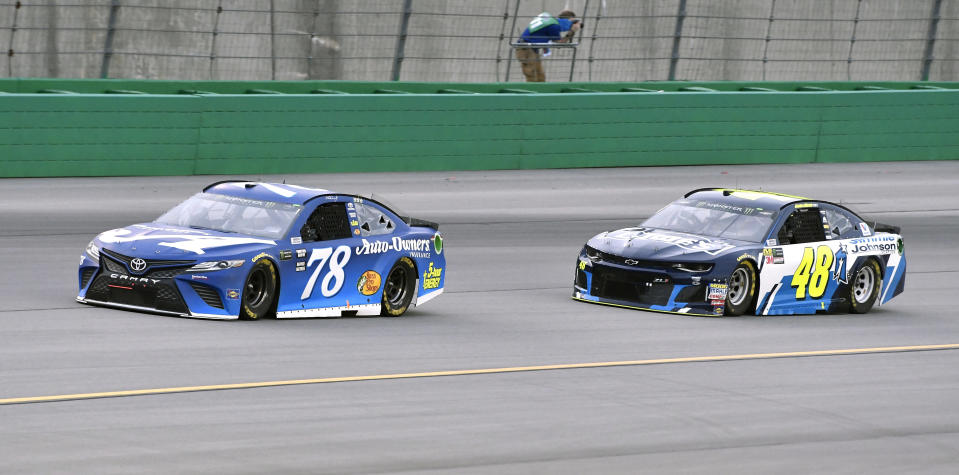 Martin Truex Jr. (78) leads Jimmie Johnson (48) into Turn 1 during the NASCAR Cup Series auto race at Kentucky Speedway, Saturday, July 14, 2018, in Sparta, Ky. (AP Photo/Timothy D. Easley)