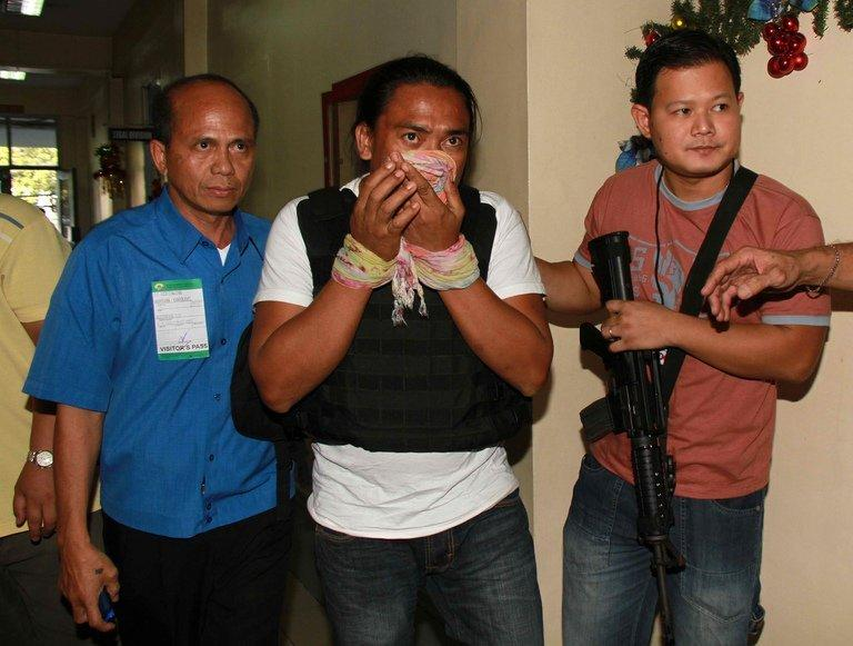 Maguindanao massacre suspect Bong Andal (centre), is escorted at the airport in Manila on November 27, 2012