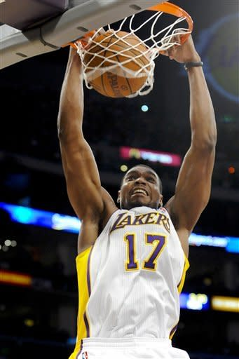 Los Angeles Lakers center Andrew Bynum dunks in the first half of an NBA basketball game against the Boston Celtics, Sunday, March 11, 2012, in Los Angeles. (AP Photo/Gus Ruelas)