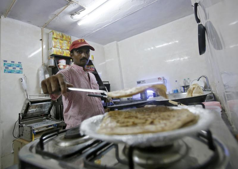An inmate prepares food inside the kitchen of a restaurant run by Tihar Jail authorities in Delhi