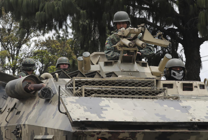 Soldiers in a fast-moving convoy ride in an armored vehicle during a 24-hour military curfew after violent protests across Quito, Ecuador, Sunday, Oct. 13, 2019. The government and indigenous protesters planned to begin negotiations aimed at defusing more than a week of demonstrations against a plan to remove fuel subsidies as part of an International Monetary Fund austerity package. (AP Photo/Dolores Ochoa)