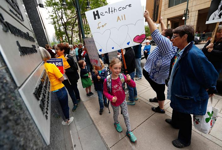 <p>People march during a protest against the Republican health bill unveiled in the U.S. Senate to dismantle the Affordable Care Act on Friday, June 23, 2017, in downtown Denver. More than 100 protesters crowded the sidewalk outside the building in which Sen. Cory Gardner, R-Colo., has his office. (Photo: David Zalubowski/AP) </p>