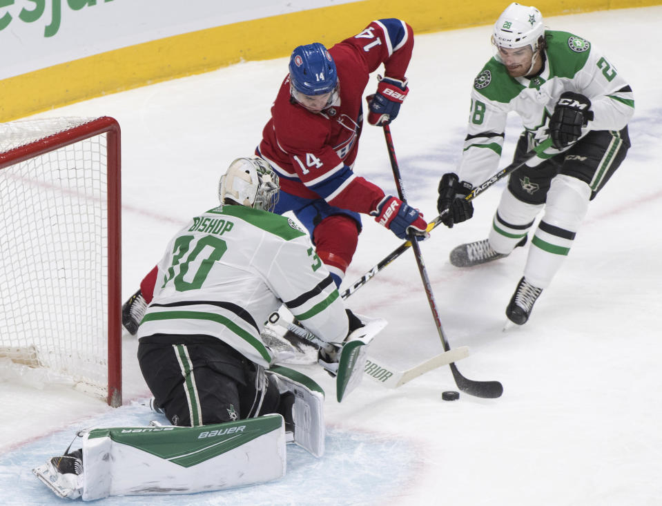 Montreal Canadiens' Nick Suzuki (14) moves in on Dallas Stars goaltender Ben Bishop as Stars' Stehpen Johns (28) defends during the first period of an NHL hockey game Saturday, Feb. 15, 2020, in Montreal. (Graham Hughes/The Canadian Press via AP)