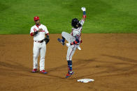 Atlanta Braves' Ronald Acuna Jr., right, playfully leaps at Philadelphia Phillies second baseman Jean Segura after hitting a double off pitcher Zack Wheeler during the sixth inning of a baseball game, Friday, Aug. 28, 2020, in Philadelphia. (AP Photo/Matt Slocum)