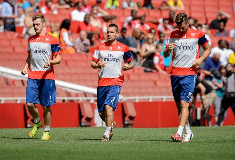 Arsenal players Calum Chambers (L), Mathieu Debuchy (C) and Olivier Giroud (R) warm up during a training session at the Emirates stadium in north London, on August 7, 2014