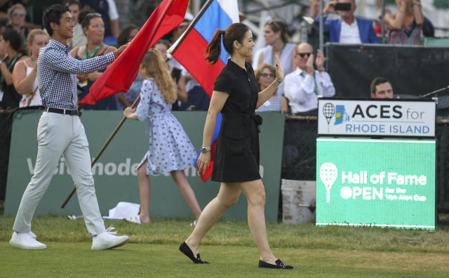 Tennis Hall of Fame inductee Li Na, of China, waves to the crowd as she is introduced during ceremonies at the International Tennis Hall of Fame, Saturday, July 20, 2019, in Newport, R.I. (AP Photo/Stew Milne)