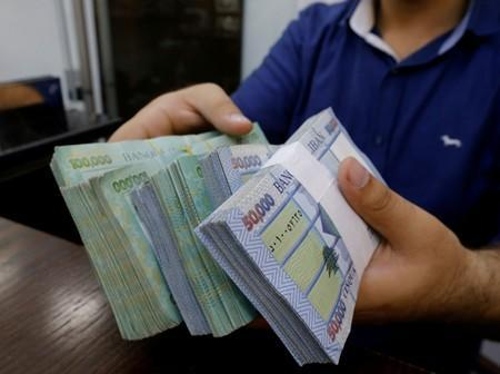 FILE PHOTO: A money exchange vendor displays Lebanese pound banknotes at his shop in Beirut