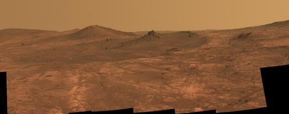 """NASA's Opportunity Mars rover captured this view of a shallow crater called """"Spirit of St. Louis"""" on March 29 and March 30, 2015. The rock spire toward the crater's far end is 7 to 10 feet (2 to 3 meters) tall."""