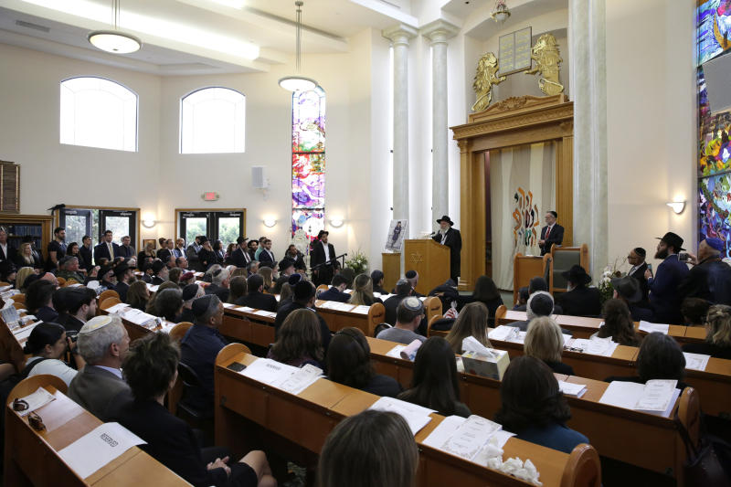 FILE - In this April 29, 2019 file photo Yisroel Goldstein, at podium, Rabbi of Chabad of Poway, speaks during a memorial service for Lori Kaye, in Poway, Calif. Search warrants released Wednesday, July 31, 2019, give the clearest indication yet that the New Zealand attacks on mosques inspired a San Diego man to open fire during a Passover service at the synagogue in April, killing one woman and injuring three others. A judge ordered the release of the warrants that authorities obtained to search the home, vehicle and online activity of John Earnest, who has pled not guilty to federal and state charges. (AP Photo/Gregory Bull, File)