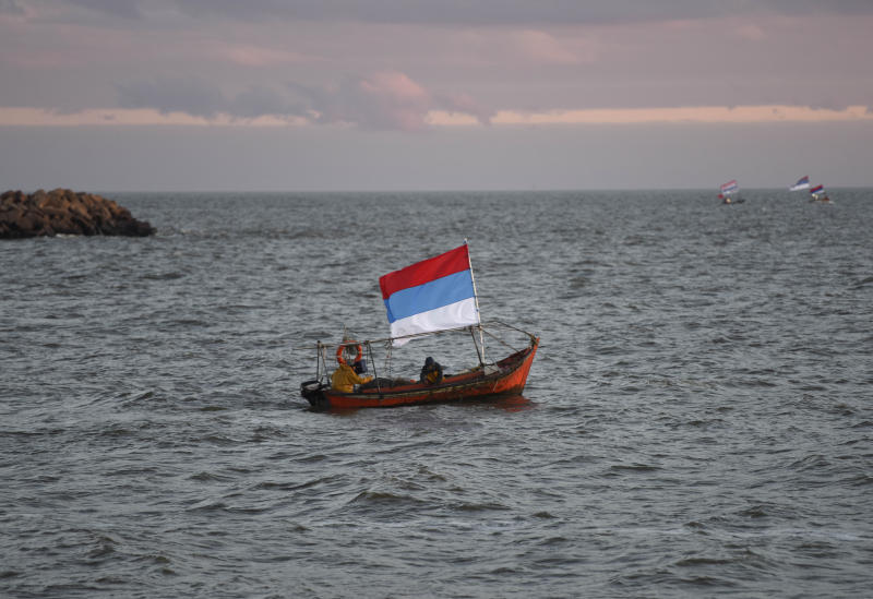 A boat flies a flag from Uruguay's ruling party Broad Front as it navigates off the coast before a closing campaign rally for presidential frontrunner Daniel Martinez in Montevideo, Uruguay, Wednesday, Oct. 23, 2019. Martinez, a former mayor of Uruguay's capital, will face off against the son of a former president in Uruguay's upcoming Oct. 27 general election. (AP Photo/Matilde Campodonico)