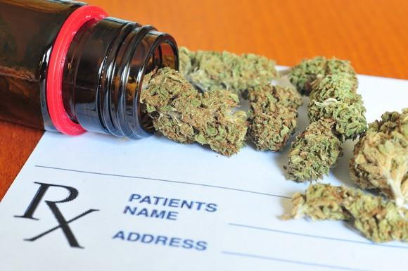 Marijuana buds spilling out of bottle on top of a prescription form