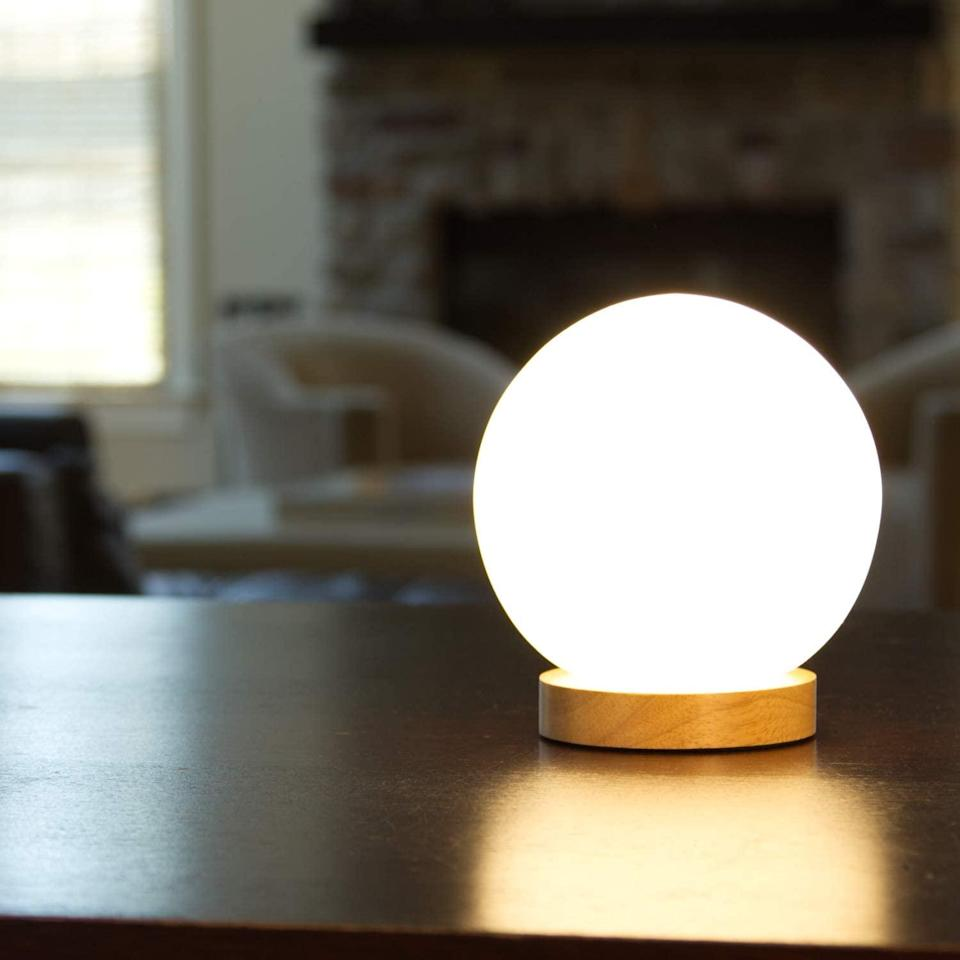 """<h3>Glass Globe Lamp</h3><br>Brighten up any dark corner of your space with this delightful glowing orb of light.<br><br><strong>Lightaccents</strong> Iris Glass Ball Table Lamp, $, available at <a href=""""https://amzn.to/3aWDB2p"""" rel=""""nofollow noopener"""" target=""""_blank"""" data-ylk=""""slk:Amazon"""" class=""""link rapid-noclick-resp"""">Amazon</a>"""