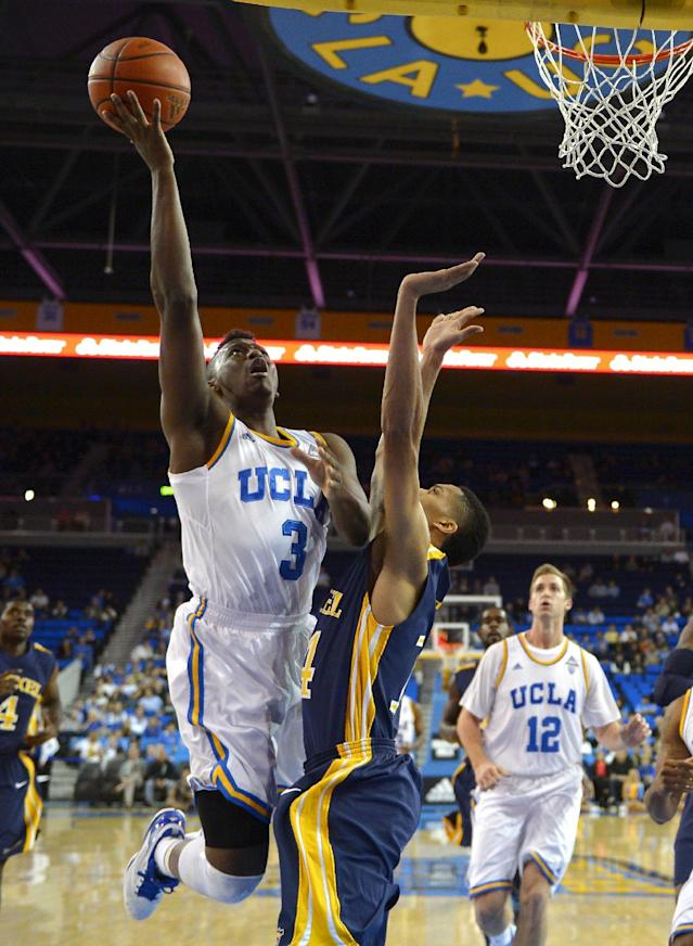 UCLA guard Jordan Adams, left, puts up a shot as Drexel guard Damion Lee, center, defends and forward David Wear looks on during the first half of an NCAA college basketball game Friday, Nov. 8, 2013, in Los Angeles. (AP Photo/Mark J. Terrill)