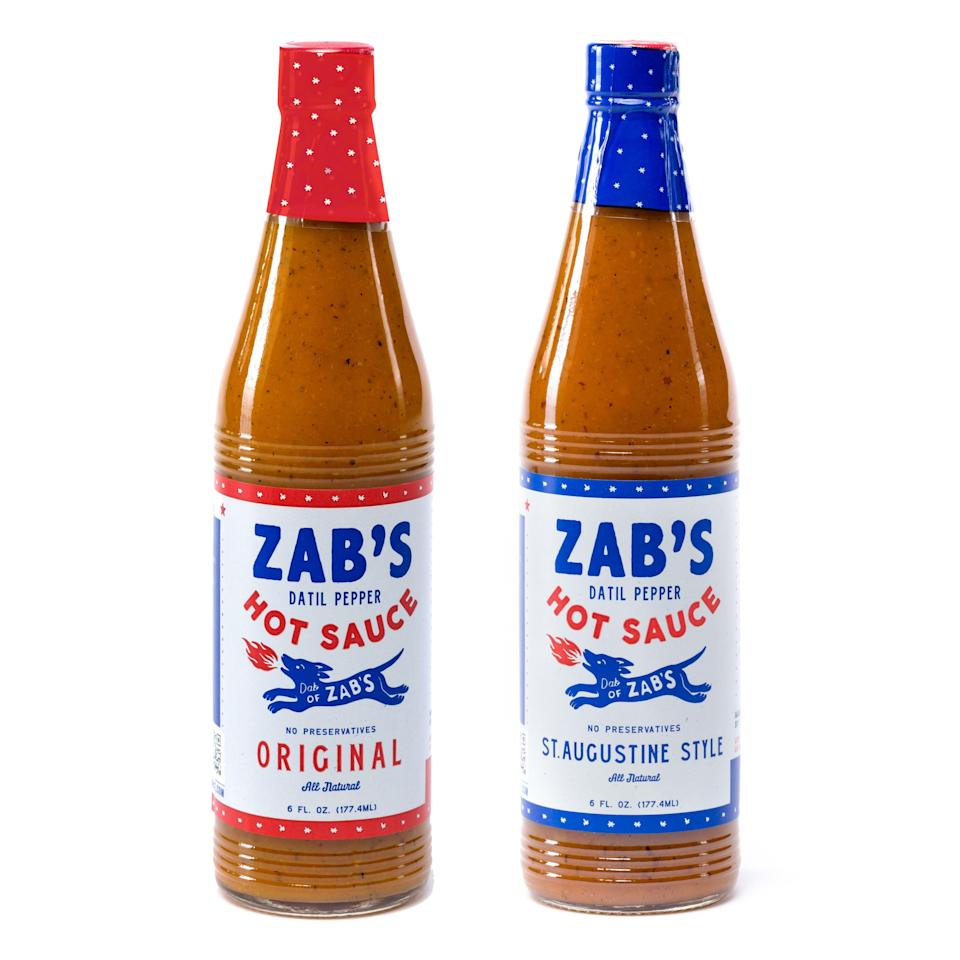 """<p><strong>Zab's Hot Sauce</strong></p><p>huckberry.com</p><p><strong>$20.00</strong></p><p><a href=""""https://go.redirectingat.com?id=74968X1596630&url=https%3A%2F%2Fhuckberry.com%2Fstore%2Fzab-s-hot-sauce%2Fcategory%2Fp%2F62928-zab-s-hot-sauce-pack&sref=https%3A%2F%2Fwww.menshealth.com%2Ftechnology-gear%2Fg36434010%2Fhot-sauce-gifts%2F"""" rel=""""nofollow noopener"""" target=""""_blank"""" data-ylk=""""slk:BUY IT HERE"""" class=""""link rapid-noclick-resp"""">BUY IT HERE</a></p><p>Aside from the hipster-chic design, Zab's hot sauce uses a rare blend of datil peppers. Straight out of Florida, they are naturally sweet with a slow rising spice. You'll get a sweet and spicy boost of flavor—a perfectly versatile companion to eggs, tacos, sandwiches, and more.</p>"""