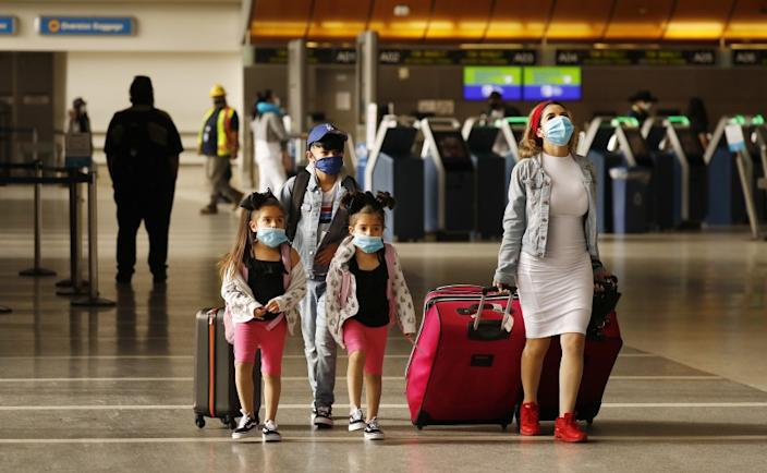 LOS ANGELES, CA - MAY 11: Yadira Barajas walks with her children Owen Vargas, 11, and 6-year-old twins Madison and Madelyn Contreras, as they prepare for a flight to Mexico at Tom Bradley International Terminal at Los Angeles International Airport (LAX) which is now requiring travelers to wear face covering to help keep fellow passengers and crew safe by limiting the spread of the coronavirus Covid-19. The new requirements for wearing face masks in Los Angels began Monday at LAX and on local public transit. LAX on Monday, May 11, 2020 in Los Angeles, CA. (Al Seib / Los Angeles Times)