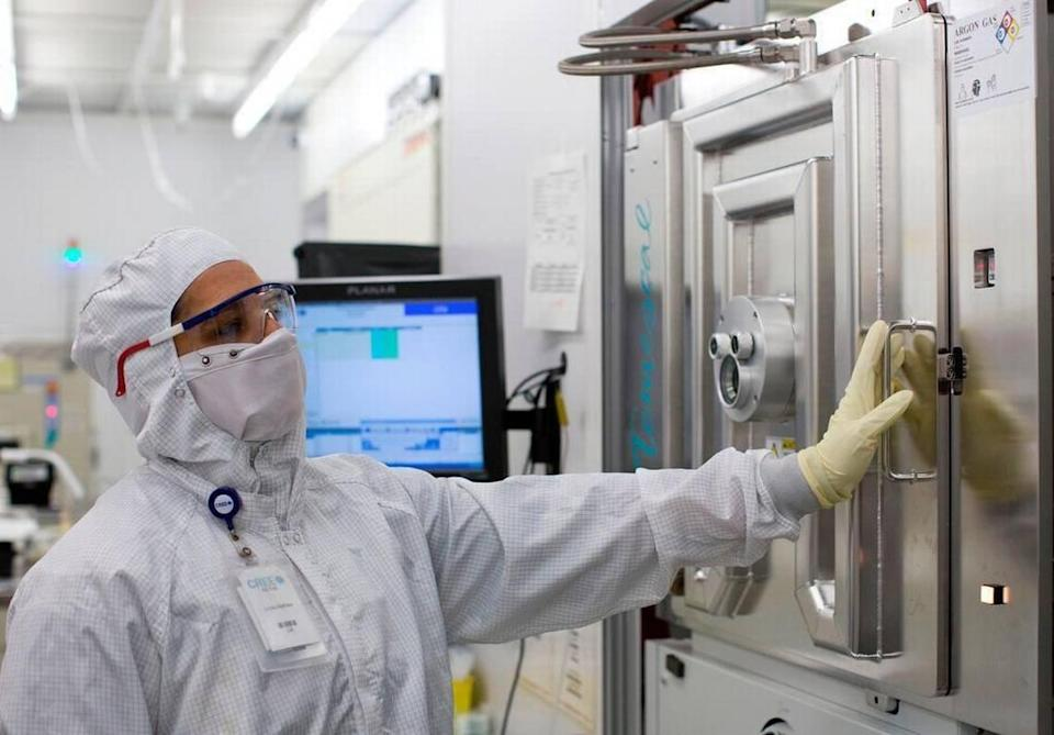 """Semiconductor Operator Linda Mathew tends to wafers inside of an evaporator machine inside of Cree's """"clean room"""" environment on Friday, August 15, 2014 in Research Triangle Park."""