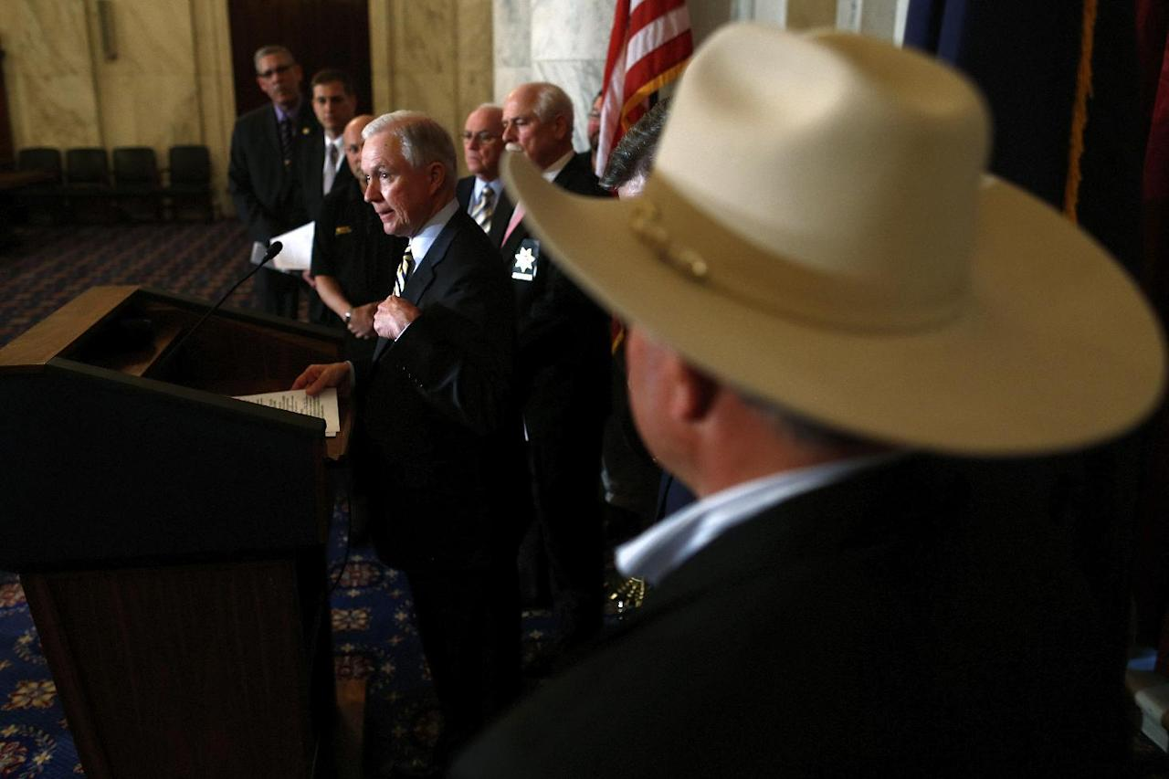 Sen. Jeff Sessions, R-Ala., stands with members of law enforcement as he speaks about immigration reform, Thursday, April 18, 2013, on Capitol Hill in Washington. (AP Photo/Charles Dharapak)