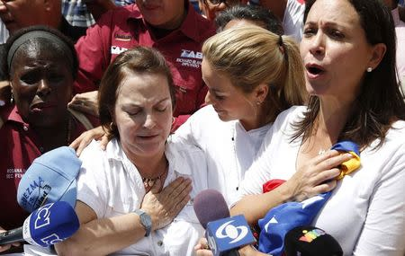 Mitzy de Ledezma (2nd L), wife of arrested Caracas metropolitan mayor Antonio Ledezma, reacts next to Lilian Tintori (2nd R), wife of jailed opposition leader Leopoldo Lopez, and opposition leader Maria Corina Machado (R), during a gathering in support of him in Caracas Febreuary 20, 2015.   REUTERS/Carlos Garcia Rawlins