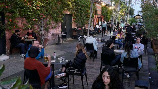 PHOTO: Diners fill the sidewalk tables in downtown Los Angeles, May 2, 2021. (Damian Dovarganes/AP)
