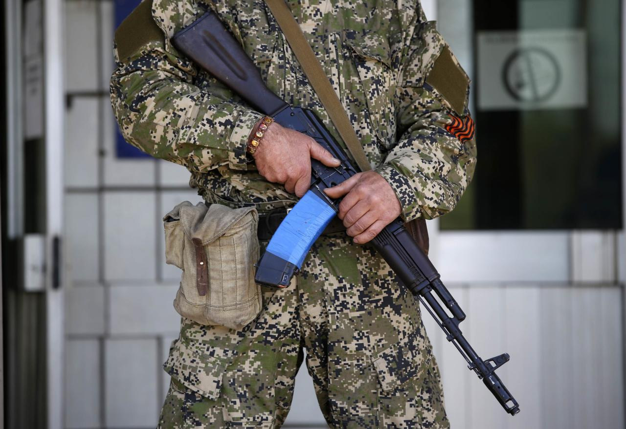 A pro-Russian armed man holds his weapon in front of the seized town administration building in Kostyantynivka April 28, 2014. Armed pro-Russian separatists who took control of the police headquarters in the east Ukrainian town of Kostyantynivka have also seized the town administration building, a spokesman for the regional government said. REUTERS/Marko Djurica (UKRAINE - Tags: POLITICS CIVIL UNREST MILITARY)
