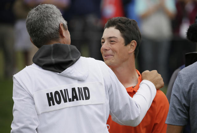 Viktor Hovland, right, of Norway, is greeted by his caddie and coach, Alan Bratton, left, on the 13th green of the Pebble Beach Golf Links after winning the USGA Amateur Golf Championship Sunday, Aug. 19, 2018, in Pebble Beach, Calif. Hovland won the match against Devon Bling. (AP Photo/Eric Risberg)