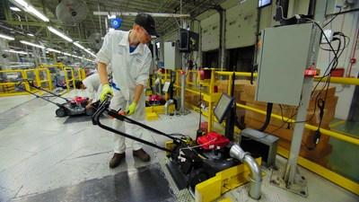 A Honda Power Equipment associate performs a quality check on a Honda lawnmower at the Swepsonville, NC plant