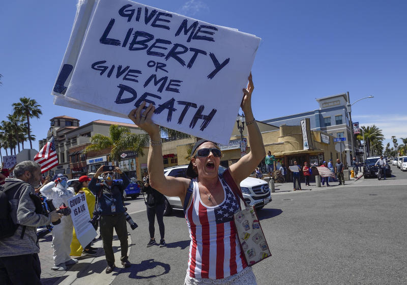 """In this Friday, April 17, 2020 photo, Sarah Mason, from Covina, joins a crowd of people gathered at the corner of Main Street and Walnut Avenue in Huntington Beach, Calif., to protest the COVID-19 coronavirus closures. On Friday, May 1, 2020, The Associated Press reported on an altered version of this photo circulating online changed to show the the sign reading, """"Barack 6 Hussein 7 Obama 5 COVID = 19 OPEN YOUR EYES."""" The actual sign reads, """"Give me liberty or give me death."""" (Jeff Gritchen/The Orange County Register via AP)"""