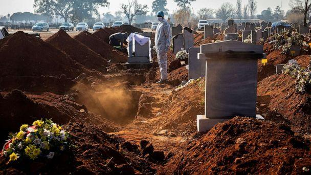 PHOTO: A family member wearing PPE looks on after the funeral of family member who died from Covid-19 at a graveyard on the 119 day of the pandemic lockdown in Johannesburg, July 24, 2020. (Kim Ludbrook/EPA via Shutterstock)