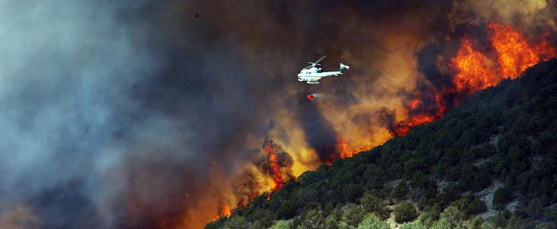 Emergency responders work on a wild land  fire that is threatening homes in Saratoga Springs, Utah,  Friday, June 22, 2012. About 1,000 homes are being evacuated after high winds kicked up a fire near a northern Utah dump. Fire officials were calling in additional aircraft to fight the fast-moving fire near Saratoga Springs and Eagle Mountain. At one point, the fire threatened an explosives factory. (AP Photo/The Deseret News, Jeffrey D. Allred)   SALT LAKE TRIBUNE OUT; PROVO DAILY HERALD OUT; MAGS OUT