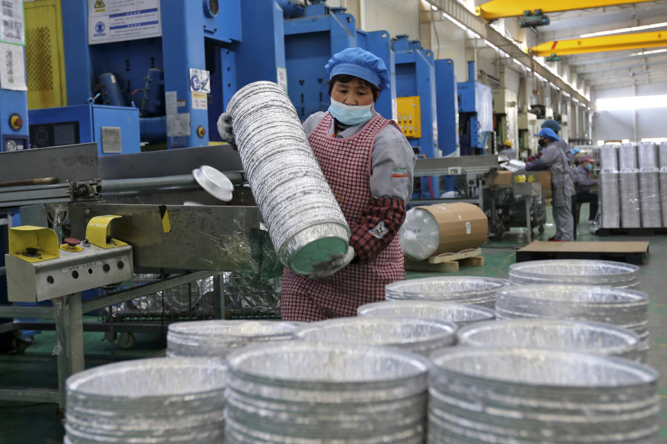 A woman wearing a face mask to help curb the spread of the coronavirus collects aluminum foil mess tins for export at a factory in Suixi in central China's Anhui province on Feb. 22, 2021. China's manufacturing recovery weakened for a third month in February as exports and new orders declined, according to two surveys released on Monday, March 1, 2021. (Chinatopix via AP)