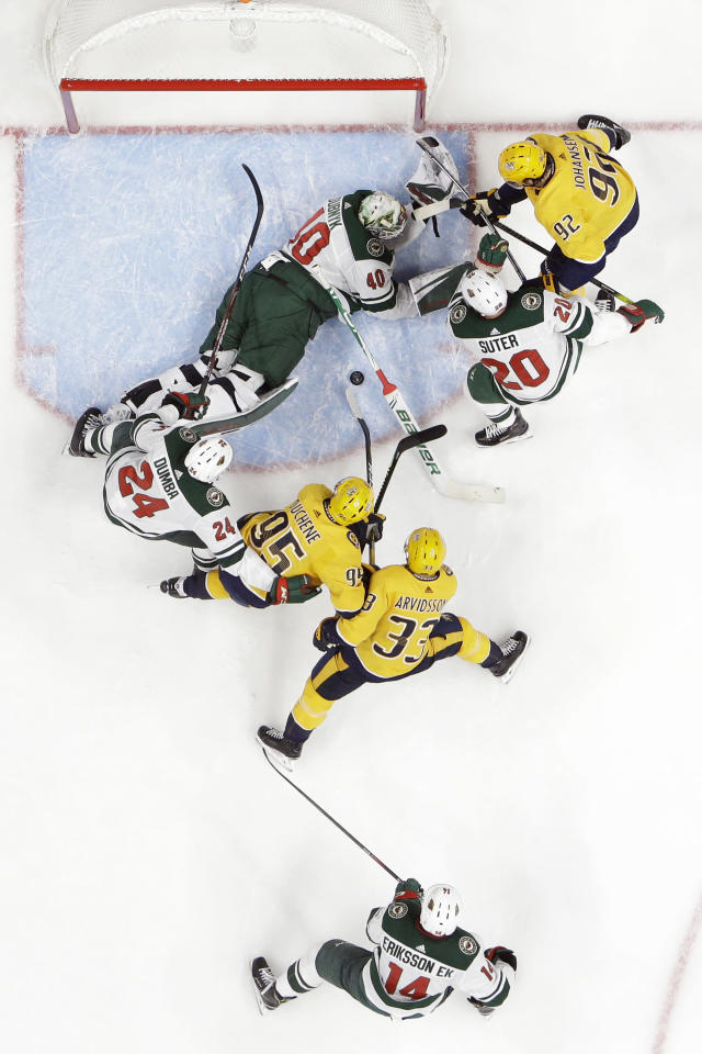 Minnesota Wild goaltender Devan Dubnyk (40) lies on the ice as he blocks the puck during a scramble in front of the net in the first period of the team's NHL hockey game against the Nashville Predators on Thursday, Oct. 3, 2019, in Nashville, Tenn. (AP Photo/Mark Humphrey)