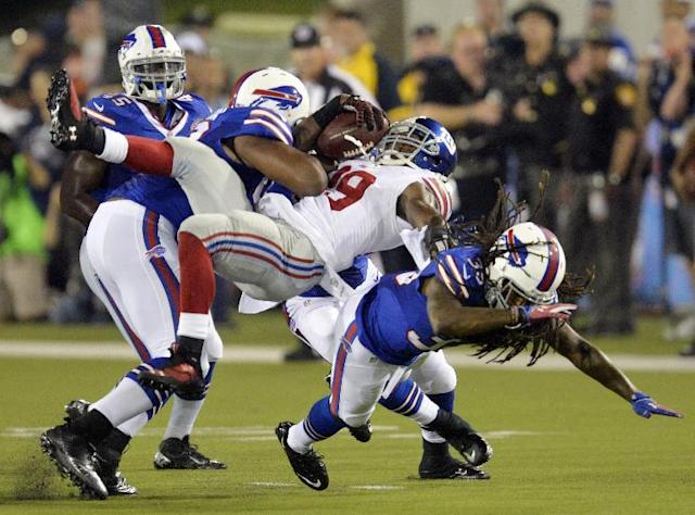 New York Giants Thomas Gordon, center, is tackled by Buffalo Bills defensive end Ikponmwosa Igbinosun, left, in the fourth quarter at the Pro Football Hall of Fame exhibition NFL football game Sunday, Aug. 3, 2014, in Canton, Ohio. (AP Photo/David Richard)
