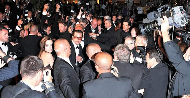 Angelina Jolie and Brad Pitt are swarmed by photographersat the 2011 Cannes Film Festival. (Photo: George Pimentel/FilmMagic)
