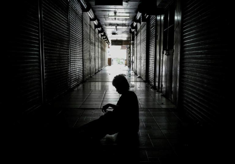 "A homeless person sleeps outside shops in the ""Roberto Huembes"" market that are closed during a 24-hour nationwide general strike called by the opposition in Nicaragua"