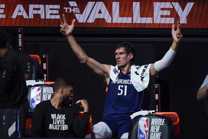 Dallas Mavericks center Boban Marjanovic with his hands raised on the bench.