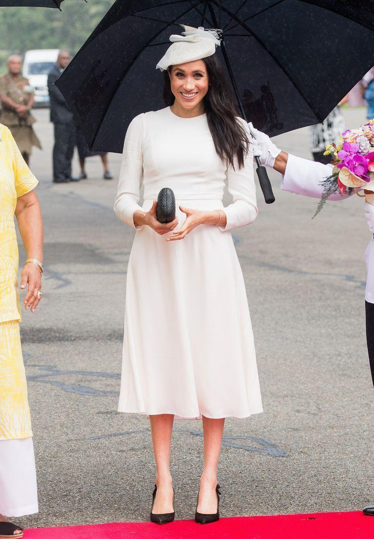 """<p>Arriving in Fiji, Meghan Markle recreated her wedding day look, opting for a formal <a href=""""https://www.net-a-porter.com/gb/en/Shop/Designers/Zimmermann/Clothing?pn=1&npp=60&image_view=product&dScroll=NaN&colourFilter=White&excludeFilters=false"""" rel=""""nofollow noopener"""" target=""""_blank"""" data-ylk=""""slk:Zimmermann ivory dress"""" class=""""link rapid-noclick-resp"""">Zimmermann ivory dress</a> with a Stephen Jones matching-coloured hat. Stepping off the plane with her husband, Prince Harry, the Duchess of Sussex looked effortlessly chic as she met with well-wishers, showing off her favourite <a href=""""https://www.net-a-porter.com/gb/en/Shop/Designers/Kayu?cm_mmc=GoogleUK--c-_-NAP_EN_UK_London-_-NAP+-+INTL+-+London+-+Designer_Kayu+-+BT--Kayu+-+Bags+-+Clutches-_-%2Bkayu+%2Bclutches_b_aud-314946096719%3Akwd-321161427809_INTL&gclid=Cj0KCQjwjbveBRDVARIsAKxH7vnRNu6gQL1Y6n9L7vmJz6nseiM8RHU_EXza9Ldrg8mIBPzxya56AoAaAn7bEALw_wcB&gclsrc=aw.ds&pn=1&npp=60&image_view=product&dScroll=0"""" rel=""""nofollow noopener"""" target=""""_blank"""" data-ylk=""""slk:Kayu box clutch"""" class=""""link rapid-noclick-resp"""">Kayu box clutch</a> and <a href=""""https://www.net-a-porter.com/Shop/Search?designerFilter=566&keywords=Tabitha+Simmons&termUsed=Tabitha+Simmons"""" rel=""""nofollow noopener"""" target=""""_blank"""" data-ylk=""""slk:Tabitha Simmons"""" class=""""link rapid-noclick-resp"""">Tabitha Simmons</a> heels for the occasion.</p>"""
