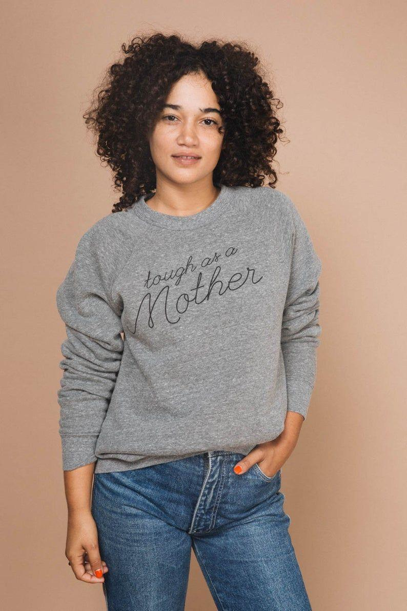 """<p><strong>TheBeeandTheFox</strong></p><p>etsy.com</p><p><strong>$54.00</strong></p><p><a href=""""https://go.redirectingat.com?id=74968X1596630&url=https%3A%2F%2Fwww.etsy.com%2Flisting%2F574255407%2Ftough-as-a-mother-womens-sweatshirt-by&sref=https%3A%2F%2Fwww.prevention.com%2Flife%2Fg35772381%2Fgifts-for-mom-from-son%2F"""" rel=""""nofollow noopener"""" target=""""_blank"""" data-ylk=""""slk:Shop Now"""" class=""""link rapid-noclick-resp"""">Shop Now</a></p><p>Let's face it: moms put up with <em>a lot</em>. Show her you appreciate all her hard work and patience with this cute sweatshirt she can wear just about anywhere.</p>"""
