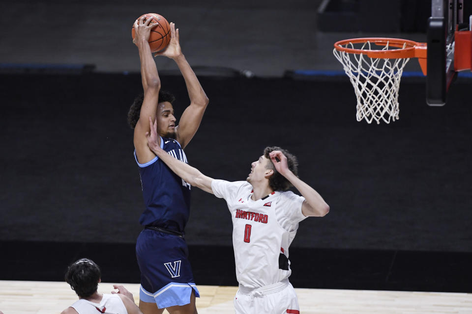 Villanova's Jeremiah Robinson-Earl, left, grabs an offensive rebound over Hartford's Hunter Marks during the first half of an NCAA college basketball game Tuesday, Dec. 1, 2020, in Uncasville, Conn. (AP Photo/Jessica Hill)