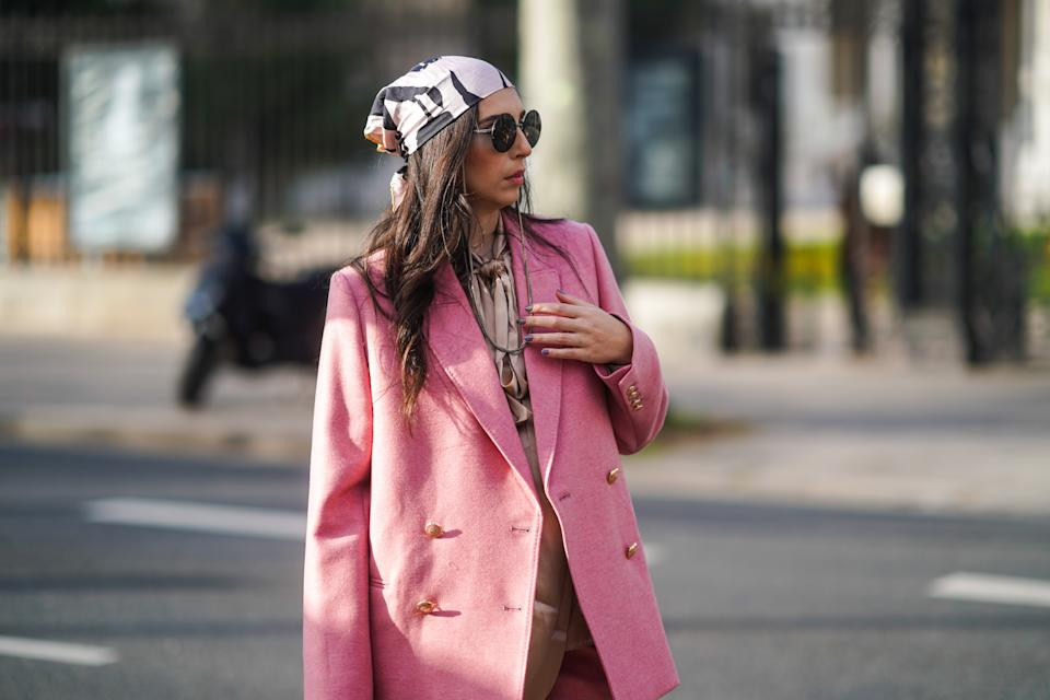 PARIS, FRANCE - FEBRUARY 23: Gabriella Berdugo wears a pink oversized suit, flare pants and silky blouse from Paul and Joe, a pink head scarf from Dior, sunglasses with a chain from Chanel, on February 23, 2021 in Paris, France. (Photo by Edward Berthelot/Getty Images)