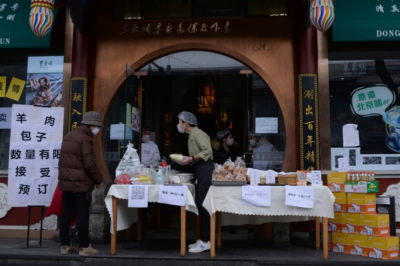 Customer wearing a face mask buys vegetable from a stall set up by a hotpot restaurant in Beijing