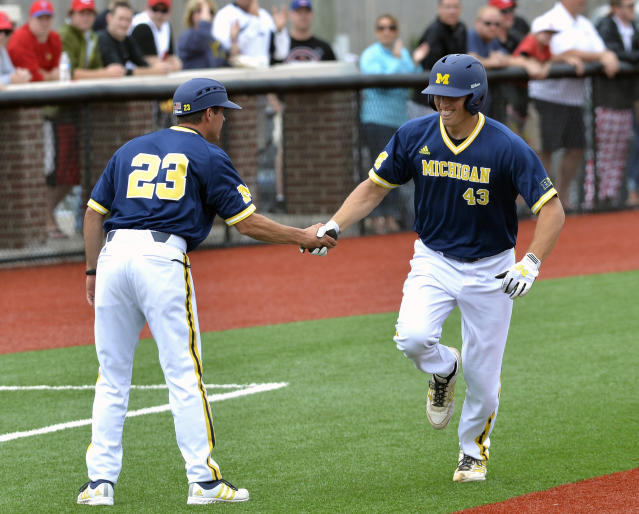 FILE - In this May 31, 2015, file photo, Michigan's Carmen Benedetti, right, shakes hands with head coach Erik Bakich while rounding the bases following his two-run home run during the first inning against Louisville in the Louisville Regional of the NCAA college baseball tournament in Louisville Ky. When Bakich took over as Michigans coach in 2012, the Big Ten was struggling to stay relevant in college baseball. There was talk that the conference should move its baseball schedule to the summer and perhaps give up on competing for NCAA titles in that sport. Instead, the league has steadily improved. (AP Photo/Timothy D. Easley, File)
