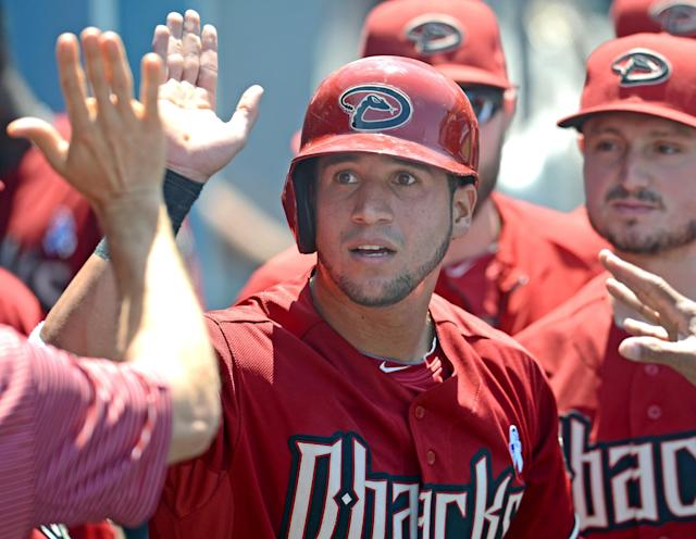 Arizona Diamondbacks' David Peralta is greeted in the dugout after scoring a run on a wild pitch by Los Angeles Dodgers' Josh Beckett in the fifth inning of a baseball game on Sunday, June 15, 2014, in Los Angeles. (AP Photo/Jayne Kamin-Oncea)
