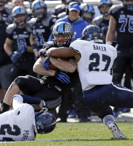 Air Force running back Mike DeWitt is wrapped up by Rice safeties Paul Porras (24) and Gabe Baker (27) after a gain during the first half of the Armed Forces Bowl NCAA college football game, Saturday, Dec. 29, 2012, in Fort Worth, Texas. . (AP Photo/LM Otero)