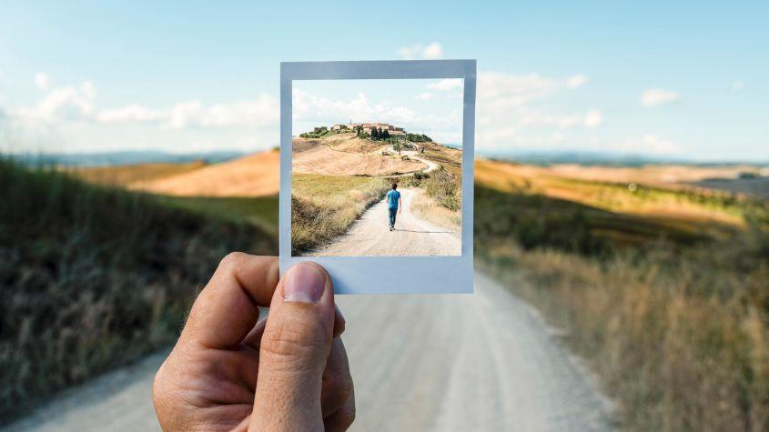 Looking through a picture frame at a boy walking down a road in the distance.