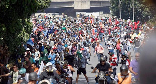 Anti-government demonstrators run in the street during a protest in Caracas, Venezuela, earlier this month. (AP)