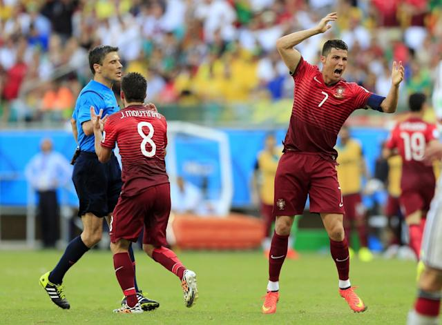 Portugal's Cristiano Ronaldo, right, and Joao Moutinho remonstrate with referee Milorad Mazic from Serbia after he refused to give a penalty during the group G World Cup soccer match between Germany and Portugal at the Arena Fonte Nova in Salvador, Brazil, Monday, June 16, 2014. (AP Photo/Bernat Armangue)