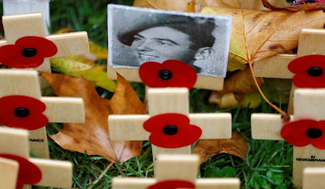 <p>A photograph of a military veteran is attached to a wooden cross in the Field of Remembrance in London, Britain, Nov. 11, 2017. (Photo: Peter Nicholls/Reuters) </p>
