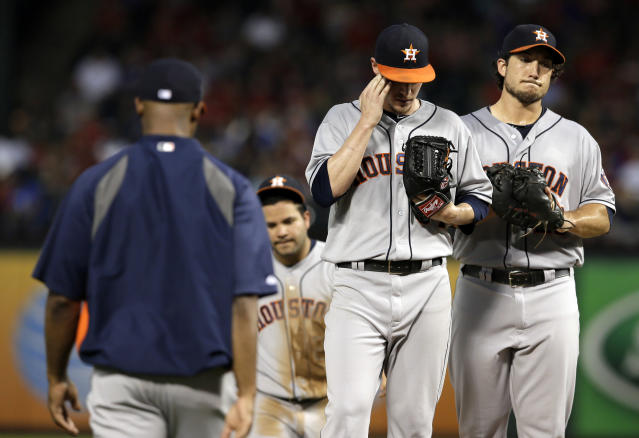 Houston Astros manager Bo Porter, left, walks out to the mound to pull starting pitcher Lucas Harrell, center, as Jose Altuve, rear, and Brett Wallace, right, watch in the third inning of a baseball game against the Texas Rangers, Monday, Aug. 19, 2013, in Arlington, Texas. (AP Photo/Tony Gutierrez)